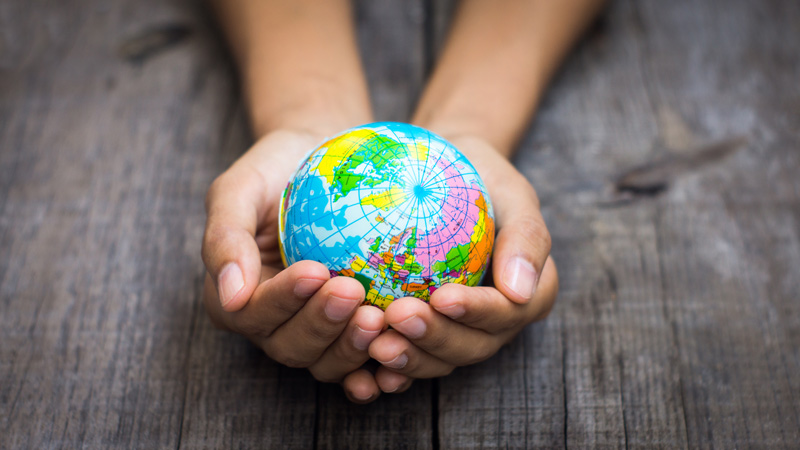 Small globe in a person's hands