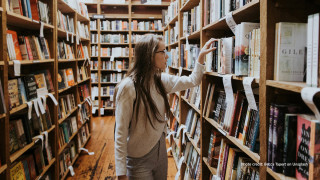 Woman searching books in a library